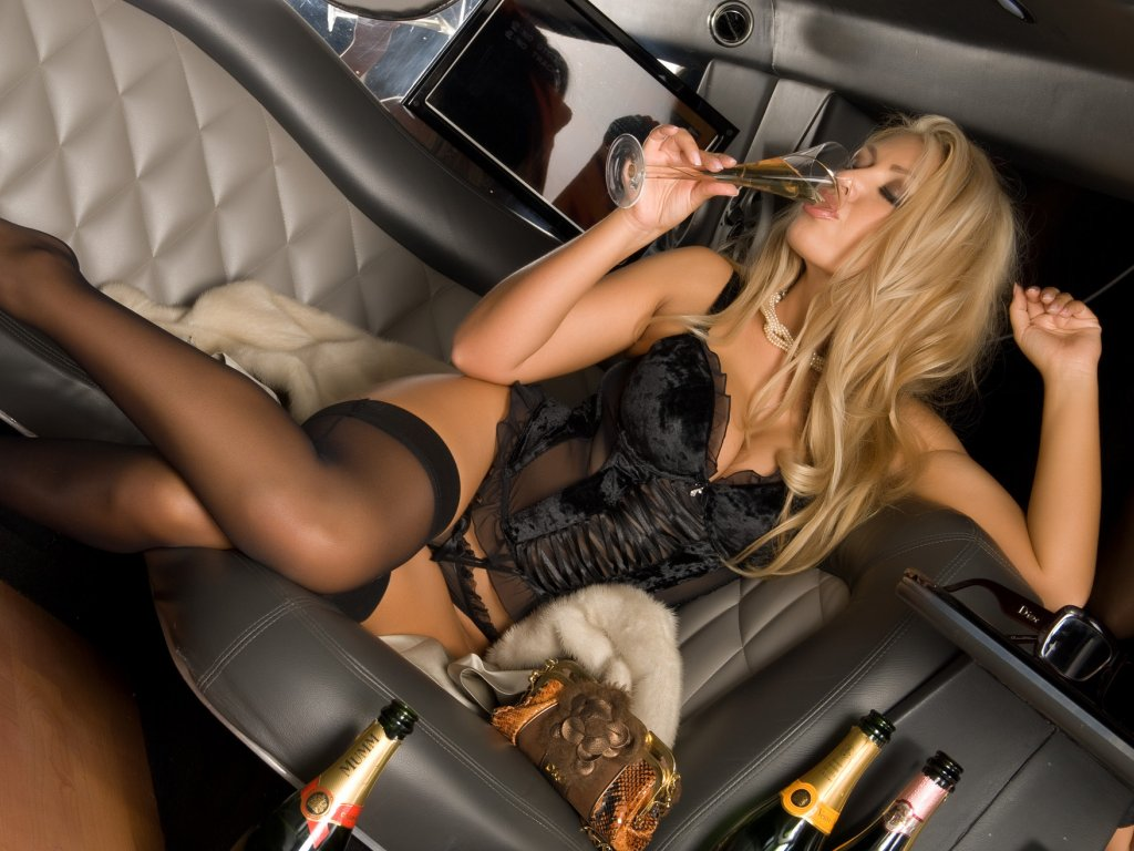 Blonde sipping champaign in a limo