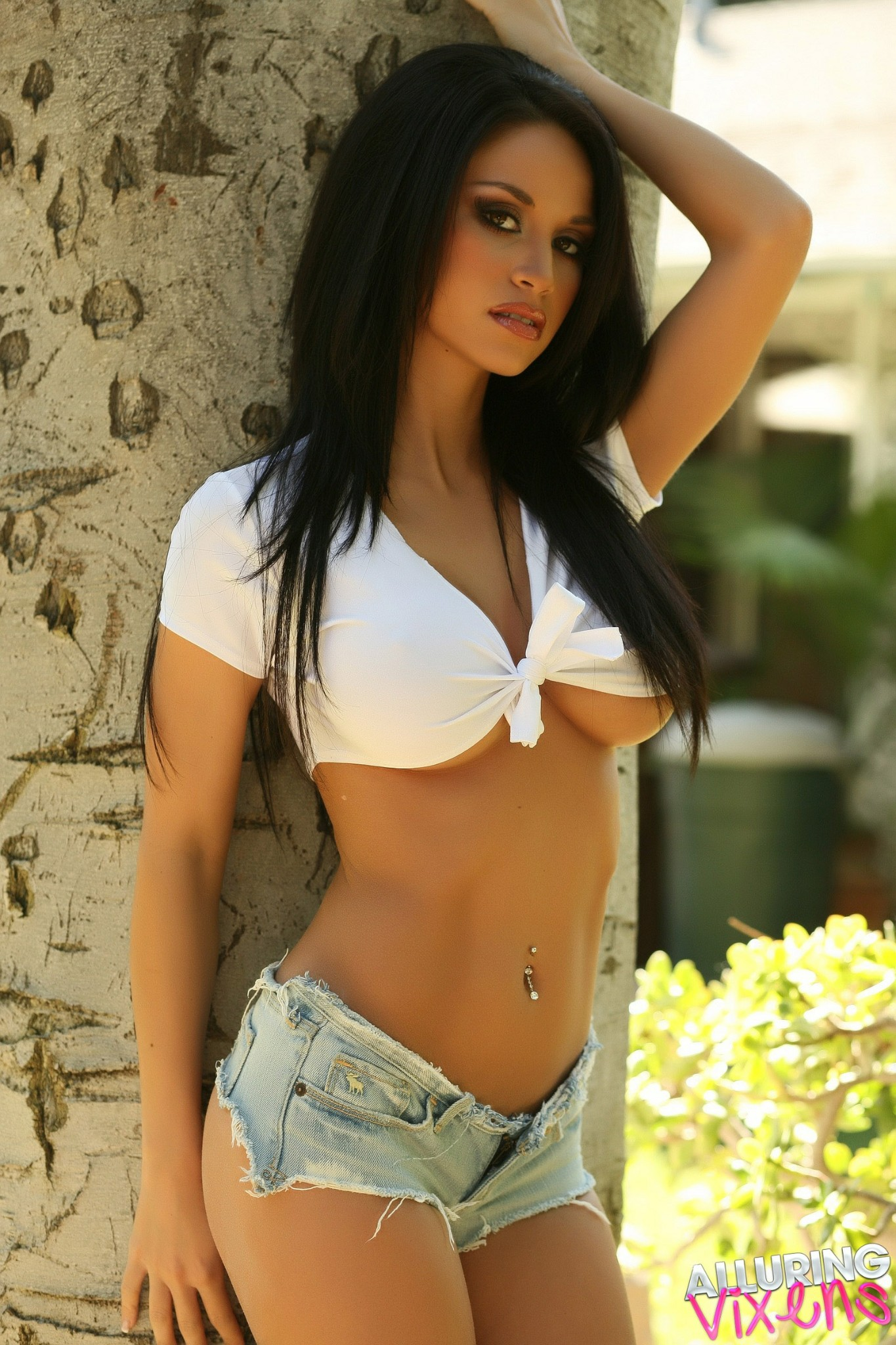 Super sexy brunette in a tied white top and jean shorts
